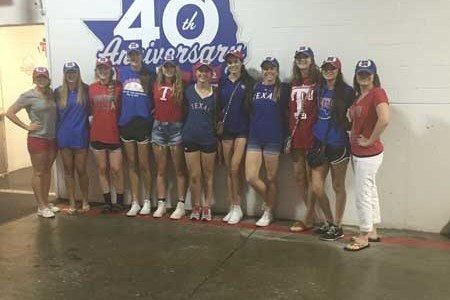 The varsity volleyball team poses in their Rangers gear.