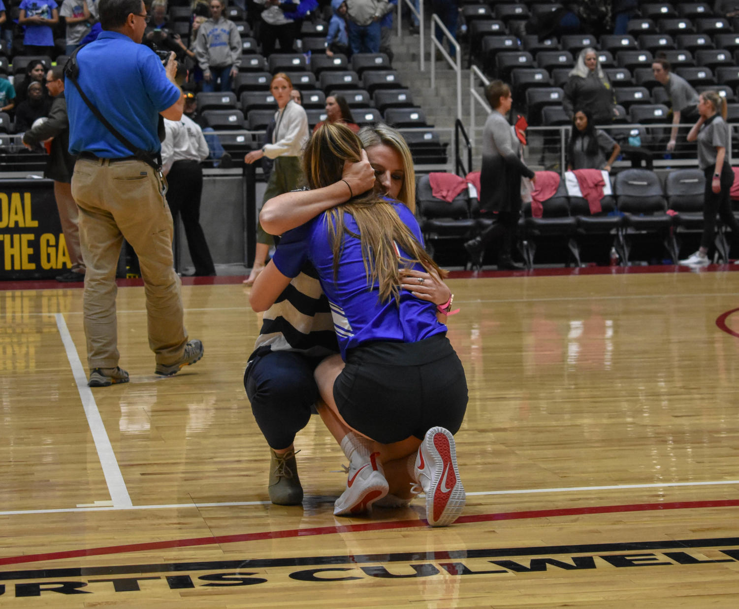 "Coach Lindsay Fallen comforts a player as the Jaguar volleyball team loses their final game. ""It was a heartbreaking loss, but moments like this are so rare and beautiful!"" Lindsay Fallen said. Kaylee Keasler (12) had just played in her last volleyball game ever, and her JV coach of two years did all she could to be there."